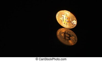 Gold bitcoin coin in focus and defocus on black background...
