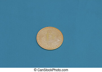 Gold bitcoin on a green background.
