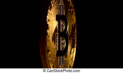 Gold Bitcoin rotates on a black background
