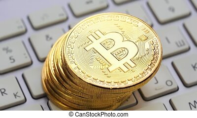Gold Bitcoin rotating on the silver keyboard. Digital coin btc money crypto currency