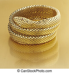 Coiled snake bracelt in gold mesh with ruby eyes on gold surface