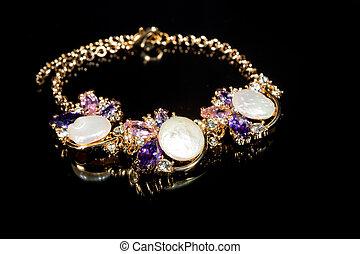 gold bracelet on black background.