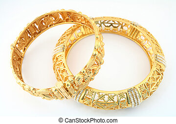 A pair of 22k gold bracelets in the Arab or Indian fashion, one of them inset with small Gulf pearls.