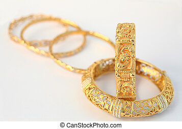 A view of Arab/Asian-style 22k gold bracelets, one of them inlaid with natural pearls. Showing the style of the workmanship.