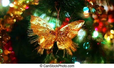 butterfly toy hangs on Christmas tree among of blinking colored garlands