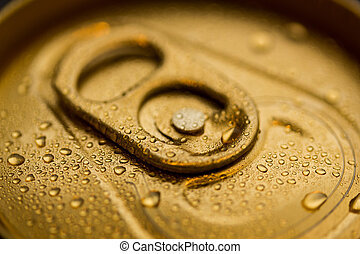 A macro close up of a sealed gold can covered with condensation