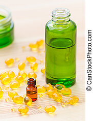 gold capsules of natural cosmetik for face and bottles with essential oils on the wooden background