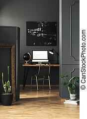 Gold chair at desk with mockup of computer desktop in grey home office interior with plants. Real photo