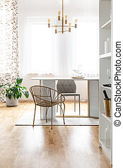Gold chair at table in white modern dining room interior with plant and lamp. Real photo