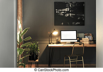 Gold chair standing by the wooden desk with lamp, notebooks and mockup computer in real photo of dark living room interior with modern poster on the wall