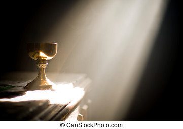Gold chalice in altar with a ray of divine light in a church