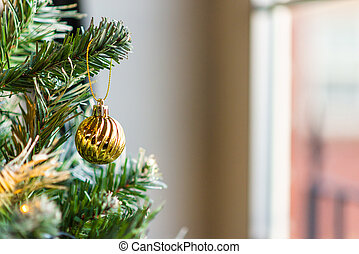 Gold christmas Bauble hanging of a green Christmas tree beside a window during the day