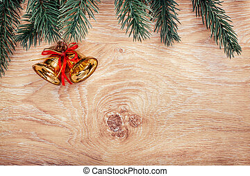 Gold Christmas bells and fir tree branch on a rustic wooden background. Xmas card and Happy New Year. Top view with copy space