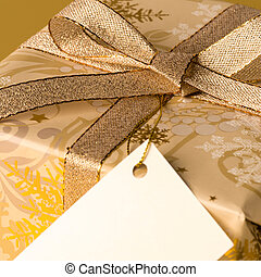 Gold Christmas present with blank tag wishing card