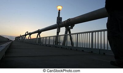 A man walks over the Gold Coast Pier during sunrise at the Spit in Queensland Australia.