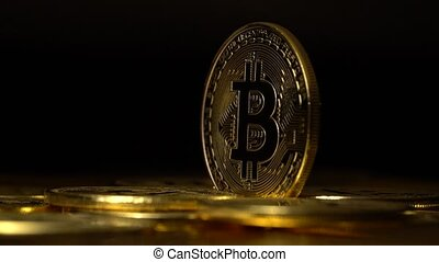 Gold coins bitcoin cryptocurrencies appear and disappear on a black background. Close up