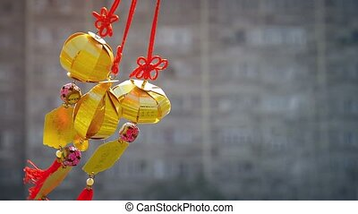 Full HD video - Three gold-colored plastic ornaments, patterned after Asian lanterns, hanging from red lanyards and plowing in a light breeze.