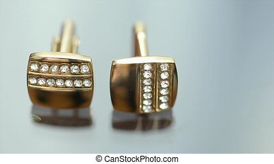 Gold Cufflinks are On a Glass Table