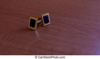 gold cufflinks lie on wooden floor.