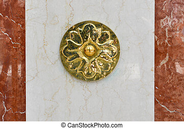 Gold decoration in the shape of a flower on a marble slab. Volumetric, shiny, carved, beautiful engraving on a white-brown stone wall. Texture. The background.