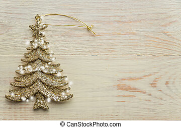 Gold decorative christmas tree toy  on wooden background. Festive New Year winter concept