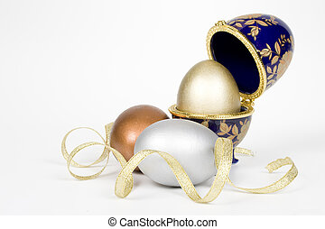 Gold egg in a glass eggcup with bronze and silver eggs