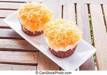 Gold egg yolk thread cakes on white dish