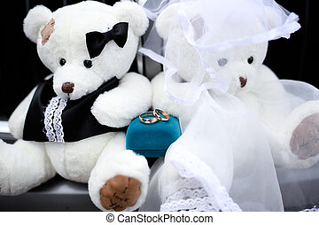 Gold engagement ring bears in a wedding dress