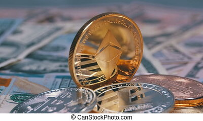 Gold Ethereum Coin, ETH and Bills of Dollars are Rotating. Different Crypto Currency Close-up. Macro. Dollar banknotes of various denominations on which lies the cryptocurrency.