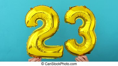 Gold foil number 23 twenty three celebration balloon on blue...