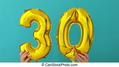 Gold foil number 30 thirty celebration balloon on a blue...