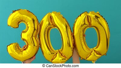 Gold foil number 300 three hundred celebration balloon on a...