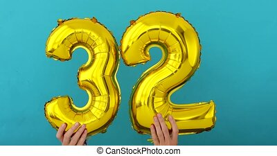 Gold foil number 32 thirty two celebration balloon on blue...