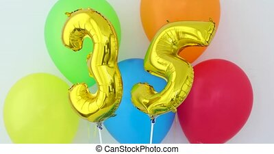 Gold foil number 35 celebration balloon on a color...