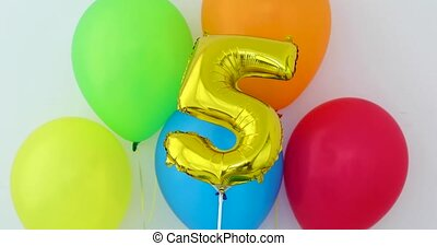 Gold foil number 5 celebration balloon on a color background
