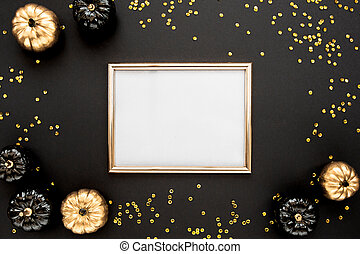 Gold frame decorated with black and gold Halloween pumpkin with copy space for text. isolated on white background. Flat lay, top view.