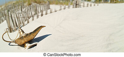 Gold genie lamp on beach dune with beach dune erosion fence in background. Genie lamp base slightly buried in sand. Pano with lamp in foreground and white sand on the right side. Erosion fence is soft and out of focus.