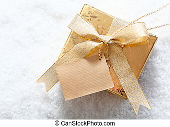 Gold gift box with blank tag in snow