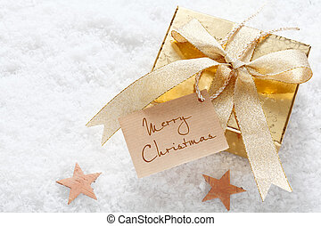 Gold gift with a decorative ribbon and Merry Christmas tag nestling on fresh snow with stars and copyspace