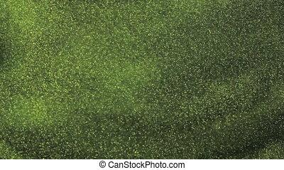 Gold glitter in green water
