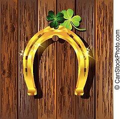Gold horseshoe with Shamrock on wooden