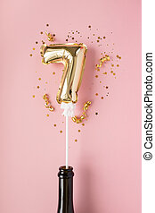 Gold inflatable number 7 on a stick with gold confetti on a pink background.