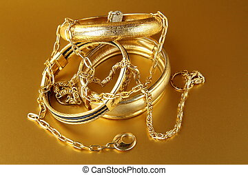 gold jewelry, bracelets and chains  on gold background