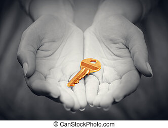 Gold key in woman's hand in gesture of giving. Concept of success in live, business solution, real estate etc