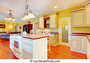 Gold kitchen with white antique cabinets.
