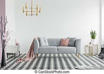 Gold lamp above grey sofa with pink blanket in spacious apartment interior with plants. Real photo