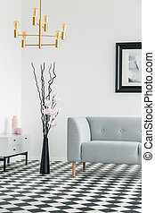 Gold lamp above plant between cabinet and grey settee in living room interior with poster. Real photo