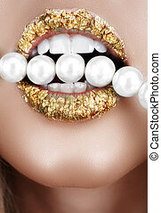 Woman open mouth with gold leaf make-up and teeth biting on faux pearls.