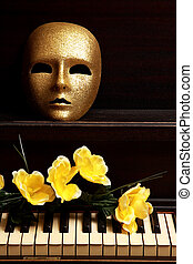gold mask on piano - gold mask and yellow flower on a piano