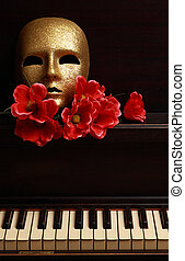 gold mask on piano - gold mask and red flower on a piano